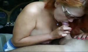 redhead mom in sunglasses is staying on her knees and sucking a manhood